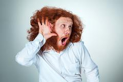 Portrait of screaming young man with long red hair and shocked facial expression Stock Photos