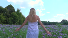 Woman walking in lilac flowers Stock Footage