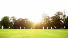 English cricket, bowler bowls to batter. Sunset in background. Stock Footage