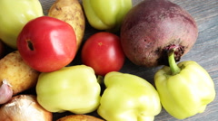 Fresh root vegetables, paprika, tomatoes and greens on a wooden table. Stock Footage