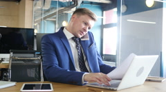 Businessman doing multitasking , working with documents , laptop and phone Stock Footage