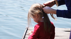 Mother girl braids hair on nature Stock Footage