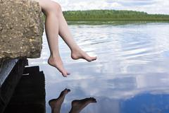 Legs dangling over water Stock Photos