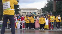 Young Asians in various costumes posing for group photo near UN Office at Geneva Stock Footage