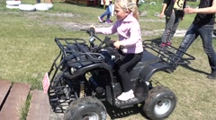 Small girl drives quad bike Stock Footage