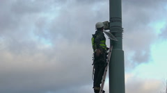 Electrical engineer checking wires, fixing street light system, dangerous job - stock footage