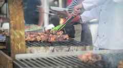 Street food - cook prepares meat on the grill - smoke, charcoal, barbecue Stock Footage