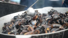 Chef cooks marine mussels in a cauldron on a street food festival - stock footage
