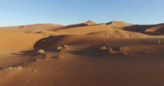 4K aerial view of male tourist walking over the sand dunes in the Namib desert Stock Footage
