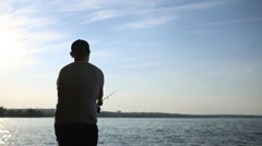 At dawn fisherman fishing on a spinning Stock Footage