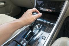 Hand on automatic gear shift, Man hand shifting an automatic car Stock Photos