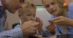 Parents and child playing with plasticine Stock Footage