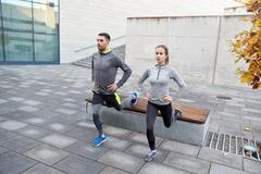 couple doing lunge exercise on city street - stock photo