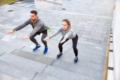 couple doing squats on city street stairs - stock photo
