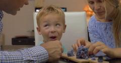 Son and parents playing with plasticine Stock Footage