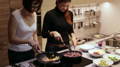 Women in a Pans Fried Meat with Vegetables Stock Footage