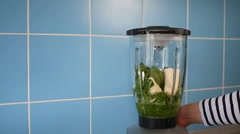Making green healthy smoothie in a glass jar on blender at home in kitchen Stock Footage