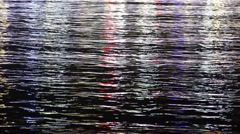 Rippling dark water surface with night lights reflection, abstract background - stock footage