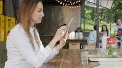 Young Pretty Business Woman Using Tablet PC on Lunch Break In An Outdoor Cafe - stock footage