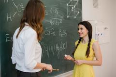 Girl answers questions of teachers near a school board Stock Photos