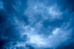 Overhead dark blue storm clouds and white areas and copy space for text overl - stock photo