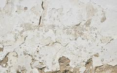 Old white painted plaster wall with cracks and stains Stock Photos