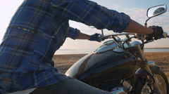Motorcyclist sitting on his motorbike on the road near the sea during sunset Stock Footage