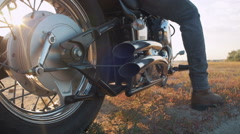 Close up shot of motorcyclist starting to drive his motorbike on the road Stock Footage