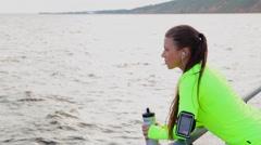 Sport woman look sea take a break drink water on city embankment - stock footage