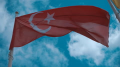 Turkish flag on the flagpole waving in the wind against a blue sky with clouds Stock Footage