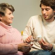 Young man giving grandmother medicament - stock photo
