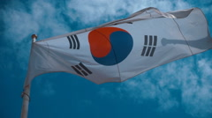 South Korean flag on the flagpole waving in the wind against a blue sky Stock Footage
