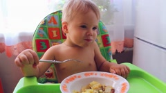 The child eats on a high chair Stock Footage