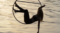 Silhouette of air gymnastics woman hanging on aerial hoop above the water - stock footage