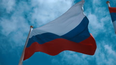 Russian flag on the flagpole waving in the wind against a blue sky with clouds Stock Footage