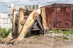 Broken and salvaged large yellow industrial machine mechanical grab frontload - stock photo