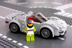 Lego Porsche driver minifigure and his car by LEGO Speed Champions - stock photo