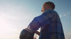 Motorcyclist putting on his helmet, dolly Stock Footage