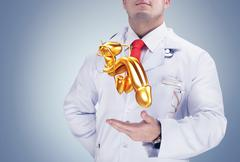 Doctor holding golden human organs on the hands on grey background. High reso Stock Photos