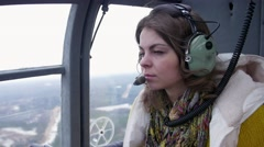 Girl in earphones with microphone seat flying helicopter. Noise. Transportation Stock Footage