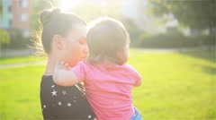 Mother and child are hugging and having fun outdoor in nature, mother hugs her - stock footage