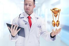 Doctor holding golden human organs and tablet in a hospital . High resolution Stock Photos