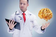 Doctor holding golden human organs and tablet on grey background . High resol Stock Photos