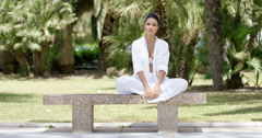 Enthusiastic woman sitting on granite bench Stock Footage