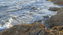 Beautiful shot of a seascape. Waves are crashing on seashore rocks - stock footage
