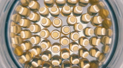 Transparent yellow medical capsules in a glass bowl is refracting light - stock footage