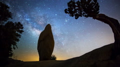 Astro Time Lapse of Milky Way over Monolith & Tree in Joshua Tree -Tilt Up- - stock footage