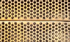 Orange rusted ventilation grill with many circular holes used as airflow for  - stock photo