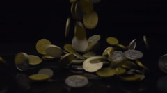 Big pile of coins fall on the table and flying away in different directions Stock Footage