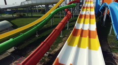 Aerial. Aquapark. Man sliding down the waterslide in a waterpark - stock footage